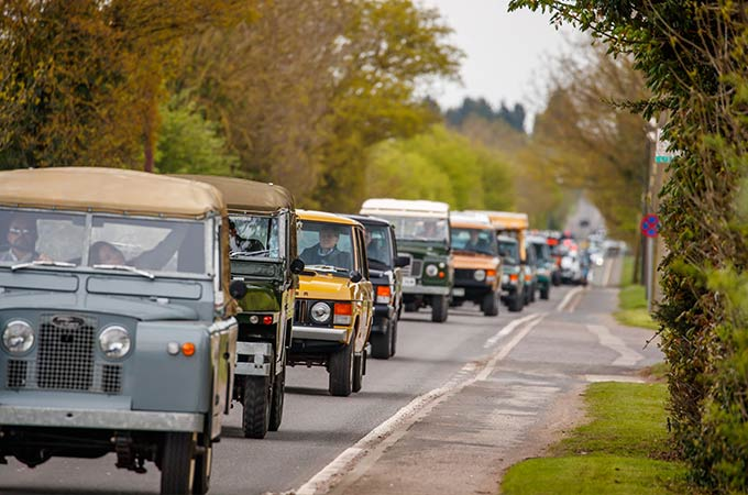 A line of classic Land Rovers and Range Rovers drive along a rural road