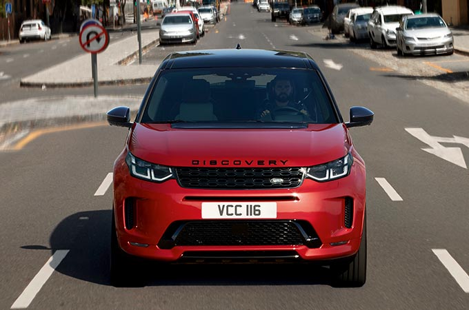 Red Discovery Sport R-Dynamic driven in city road.