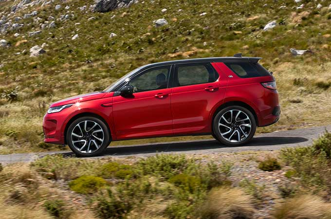 Red Discovery Sport driven down mountain road.