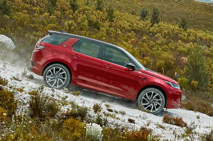 Red Discovery Sport R-Dynamic driven down gravel road.