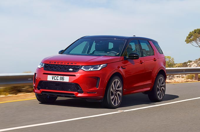 Red Discovery Sport R-Dynamic driven on mountain road.