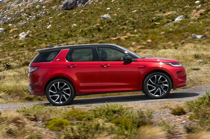 Red Discovery Sport R-Dynamic driving up mountain road.