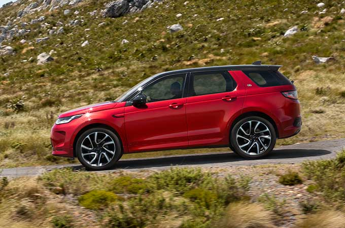 Red Discovery Sport R-Dynamic driving down mountain road.