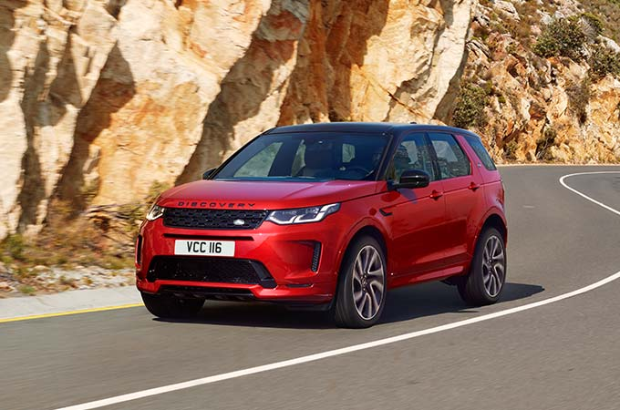 Red Discovery Sport R-Dynamic driving on mountain road.