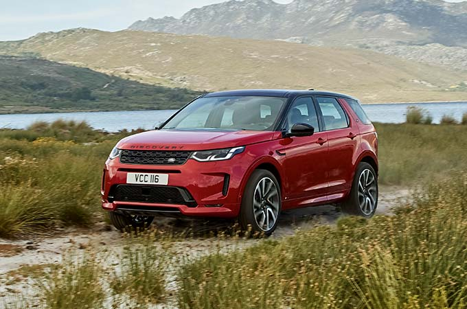 Red Discovery Sport R-Dynamic driving on dirt mountain road.