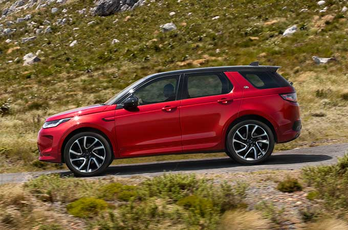 Red Discovery Sport R-Dynamic driven down mountain road.