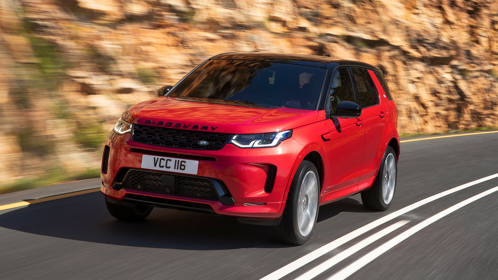 2020 Discovery Sport in motion on a mountain road front side view.