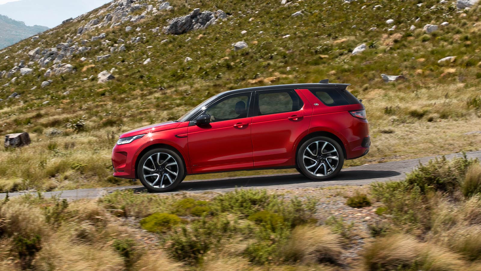 Red Discovery Sport driving through a rural area